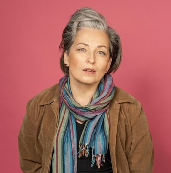 Sexy silver-haired woman looks at camera. Good-looking mature lady in multy-colored scarf posing in studio on pink background