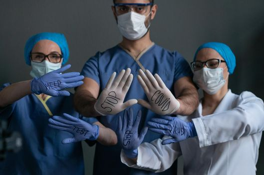 Doctors With Inscriptions On Disposable Gloves