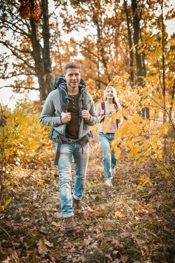 Family Hiking On Autumn Forest Footpath