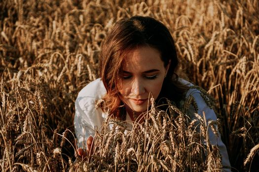 Redhead beautiful woman in a rye field. She breathes in the scent of fresh ears