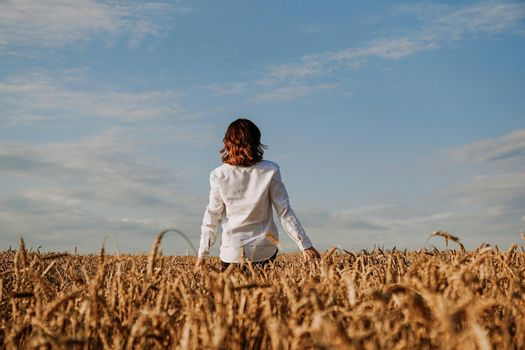 A woman in white shirt in rye field. View from the back. The concept of harmony