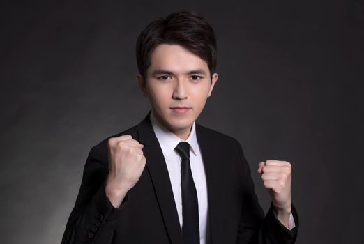 Young businessman in black suit and showing the fist