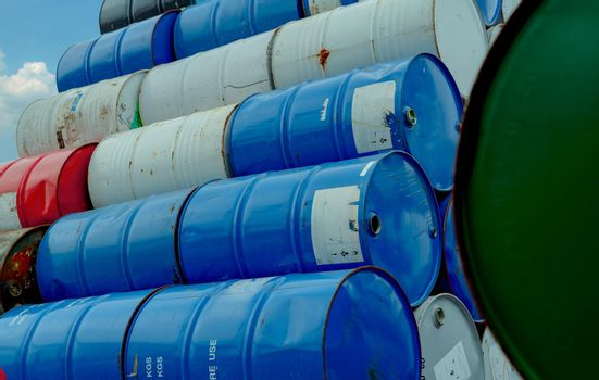 Old chemical barrels stack. Red, green, and blue chemical drum. Steel tank of flammable liquid. Hazard chemical barrel. Industrial waste. Empty chemical barrels at the factory warehouse. Hazard waste.