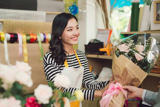 Woman selling flowers to a man