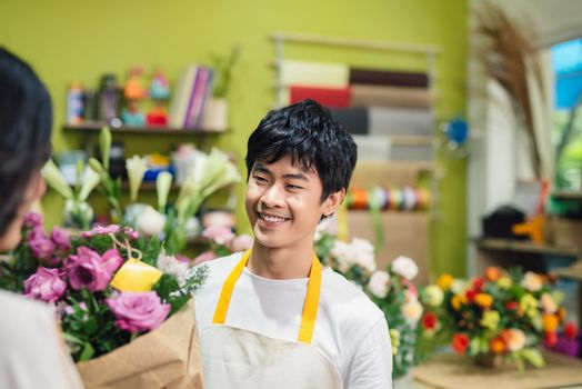 Male florist offering flowers at the counter in the florist shop