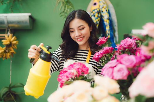 Vietnamese young flower shop owner spraying bouquets