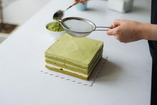 Pour green tea powder over delicious cheesecake