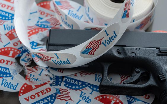 Many torn voting campaign buttons with handgun as concept for for voter suppression