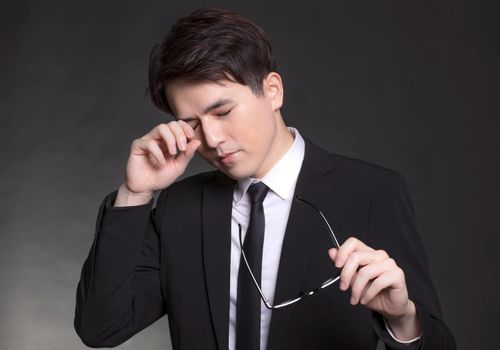 Businessman feeling sick and tired. young man rubbing eyes