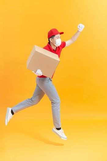 Fun jumping delivery man in red cap t-shirt uniform sterile face mask gloves isolated on yellow background
