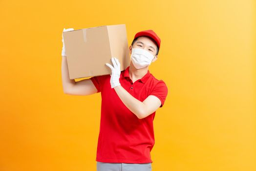 Courier in protective mask and medical gloves holding cardboard box to deliver