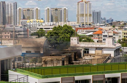 Plume of black smoke clouds from burnt abandoned building on fire at some area in the bangkok city.