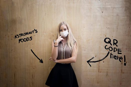 Portrait of smiling woman with mask against wall.
