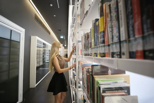 Young woman or girl standing in bookstore or library and look on book.