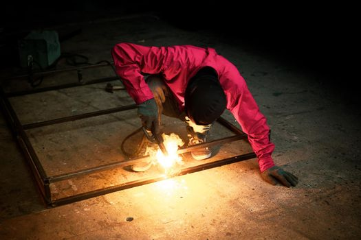 Welder used grinding stone on steel in factory with sparks, Welding process at the industrial workshop, hands with instrument in frame.
