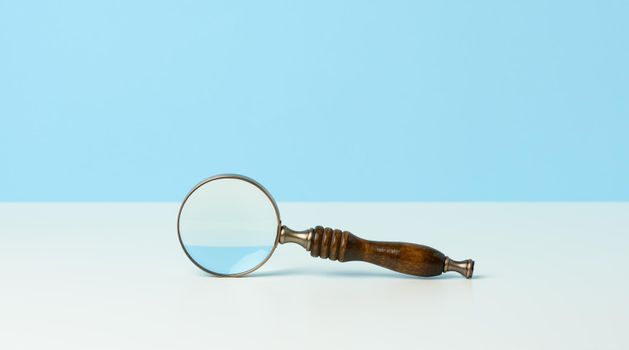 wooden magnifier on a white background. The concept of uncertainty and the search for solutions, doubts