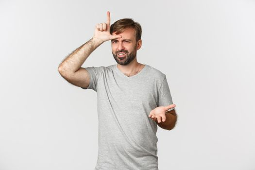 Portrait of arrogant man in gray t-shirt, mocking person who lost, showing loser sign on forehead and looking with dismay, standing over white background