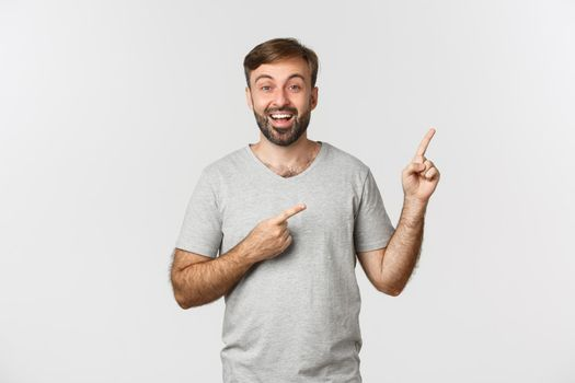Happy good-looking adult guy with beard, wearing t-shirt, pointing fingers at upper right corner, showing banner, standing over white background