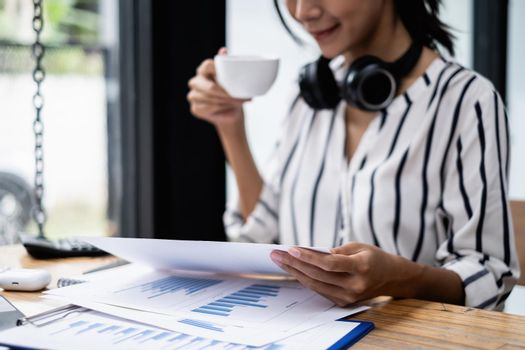 Businesswoman working to analyze technical price graph and indicator holding cup of coffee at morning.