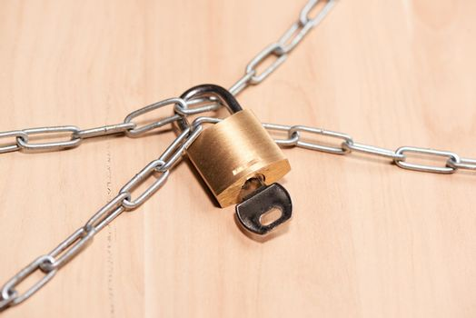Heavy chain with a padlock on table.