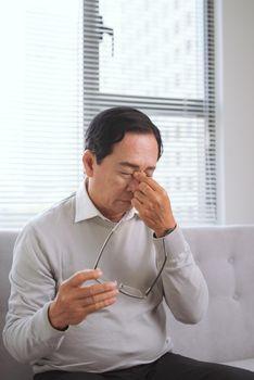 overworked senior rubs an eye in fatigue