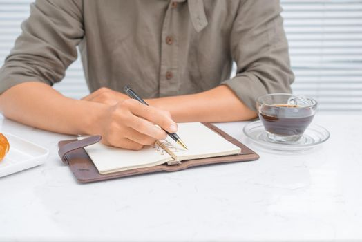 A man writing journal at home in the morning.