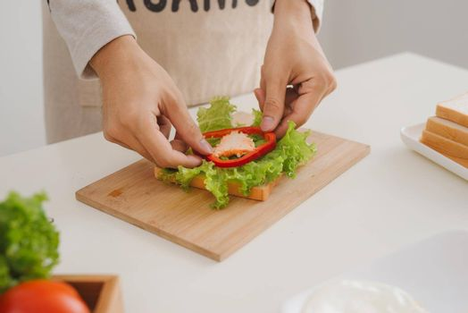 Hands of man prepare sandwich at home.