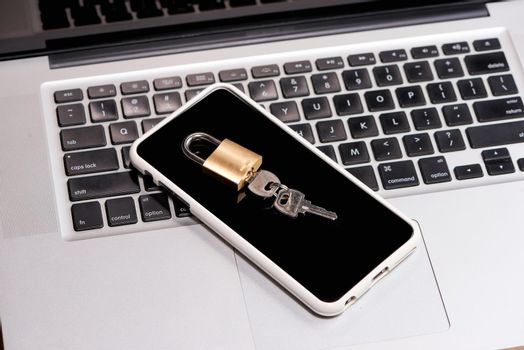 Smartphone and padlock is lying on a laptop keyboard