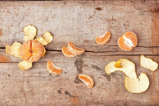 Peeled tangerine and tangerine slices on a wooden table