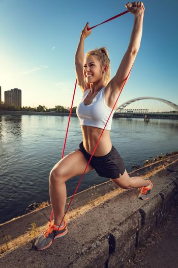 Woman doing outdoors training with resistance bands