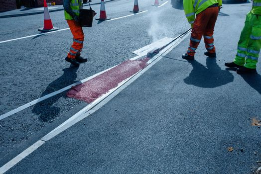 Roadworker applying thermoplastic road marking on the freshly laid tarmac during new roundabout and access road construction