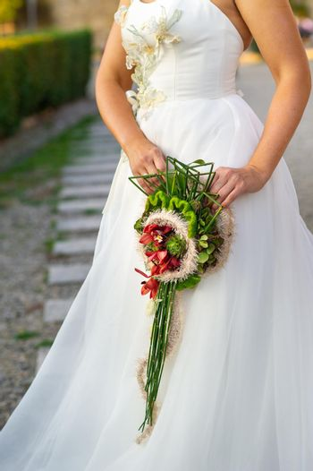 an unusual elongated wedding bouquet in the hands of the bride