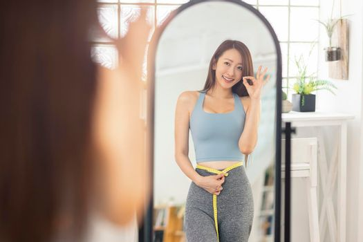 Young woman measures her waist size before mirror .With an OK gesture. Fitness.