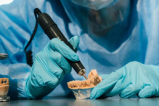 A masked and gloved dental technician works on a prosthetic tooth in his lab