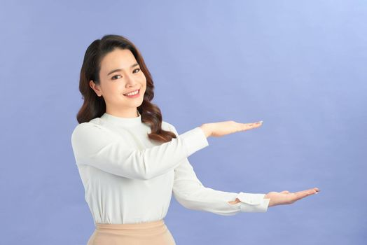 Woman in a beige skirt shows a size with her hands