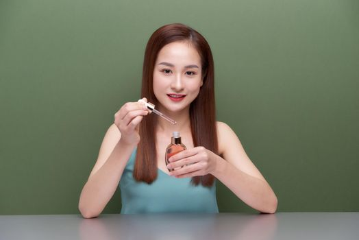 Close up asian woman 20s with perfect skin, nude make up apply oil from bottle on face isolated on green wall background