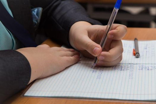 The boys hand with a fountain pen carefully solves a close-up math example.