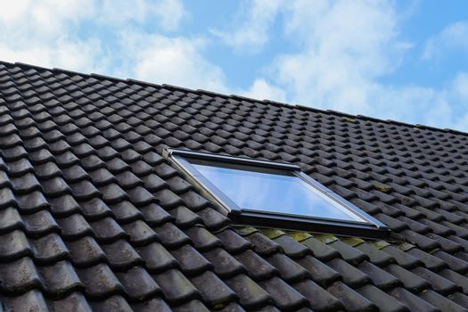 Roof window in velux style with black roof tiles.