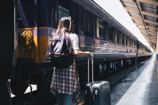 Image of a woman with a rucksack standing at a train station waiting to board a train. concept of solo travel