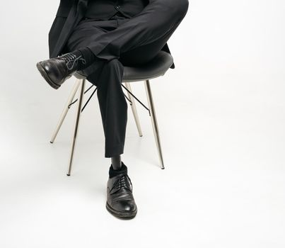 Cropped view of disabled young man with prosthetic leg sitting on a chair in studio, artificial limb concept over white background
