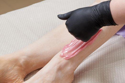 Closeup Of Beautician Waxing Woman's Leg In Beauty Spa