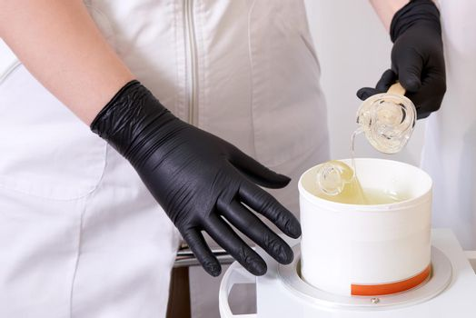Wax heater with hot yellow wax on wooden spatula in human hand. Hot wax for depilation. Salon equipment