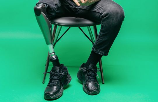Cropped view of disabled young man with prosthetic leg, artificial limb concept. Studio shooting on green background