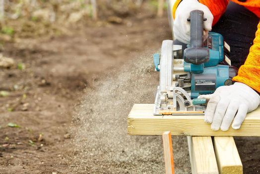 hand circular saw, carpenter sawing boards with a hand-held circular saw in the street