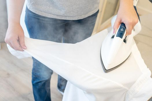 Young Woman ironing sleeve of white shirt with much steam