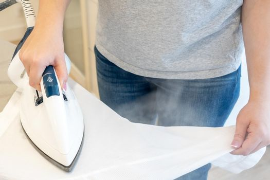 Woman ironing sleeve of white shirt with much steam