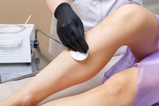 Beautician getting ready to wax female legs in spa center. Preparation for depilation