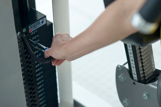 Weight adjustment on training equipment at a gym. Separating weight for adjusting to size and strength
