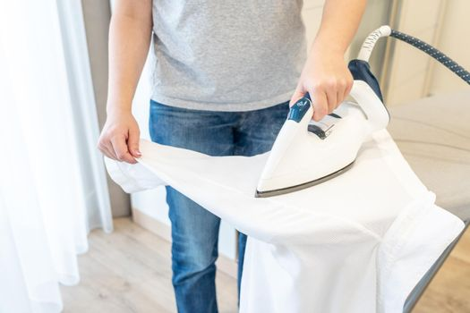 Girl ironing sleeve of white shirt with much steam