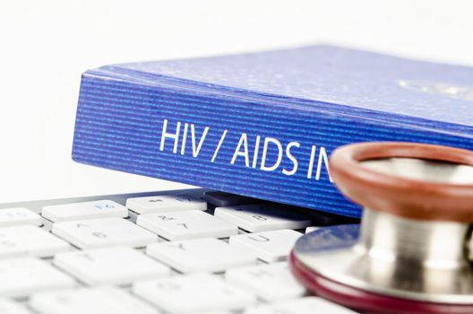 The book with HIV text and stethoscope medical on keyboard computer.